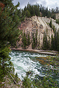 The Yellowstone River arriving at the Lower Falls, Grand Canyon of Yellowstone, in Yellowstone National Park, Wyoming. The reason for the colours of the rhyolite rocks is that they are oxidising, or rusting due to their iron content.