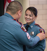 "Minhnguyet ""Nicky"" Tran smiles after her brother Tridung Tran, left, presents her with her badge during a swearing-in ceremony for new officers at the Houston ISD Police Department, March 3, 2014."