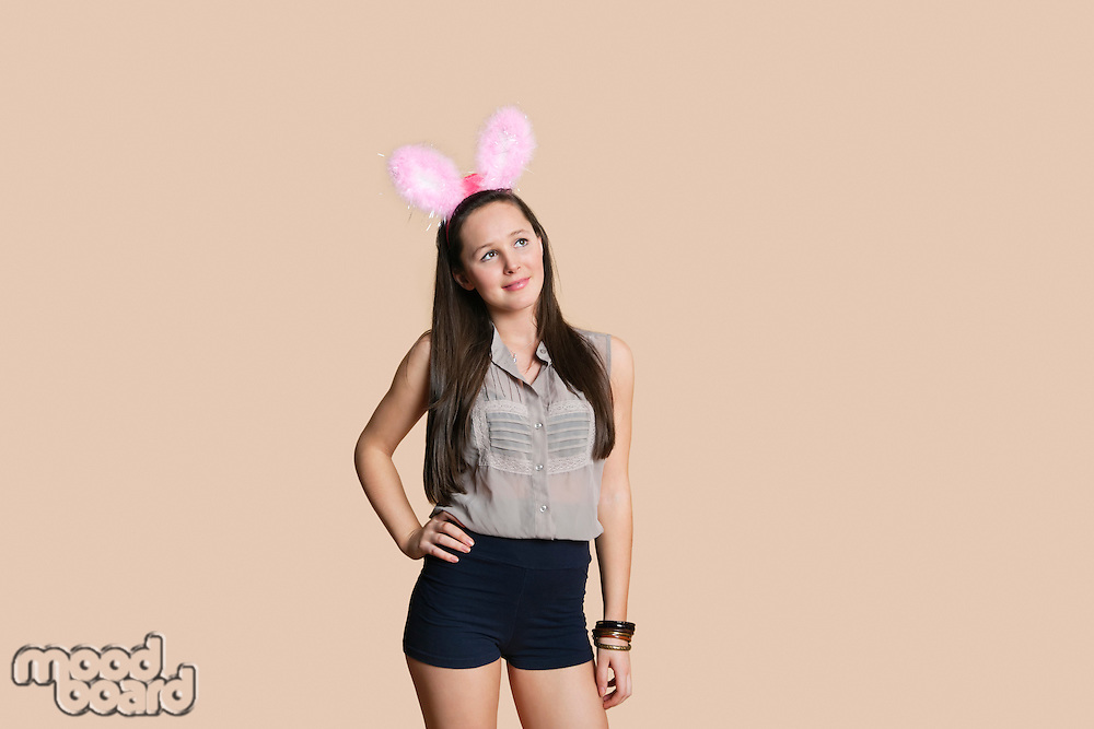 Beautiful young woman wearing rabbit ears while looking away over colored background