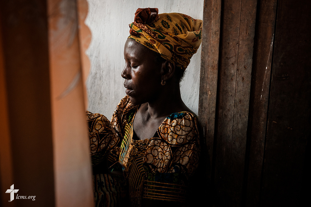 A patient prays following a devotion just as the clinic prepared to open on the third day of the LCMS Mercy Medical Team on Wednesday, May 9, 2018, in the Yardu village outside Koidu, Sierra Leone, West Africa. LCMS Communications/Erik M. Lunsford