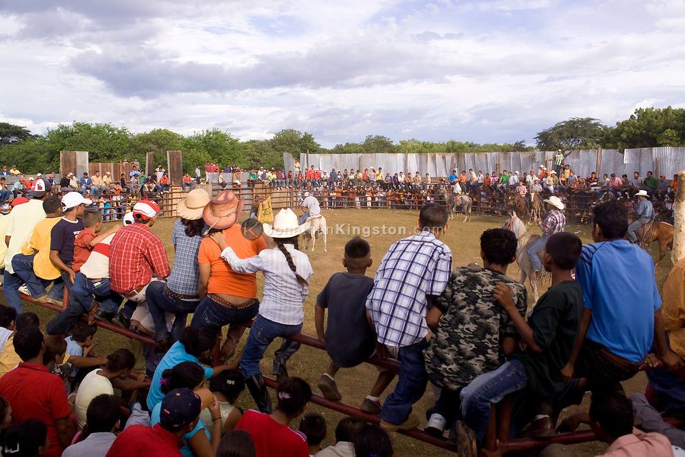 An audience crowds into a temporary stadium to watch the bullfight in Somotillo, Nicaragua. Bullfighting in Nicaragua is a combination of a rodeo and a bullfight, where one participant wears the bull down and another member, often someone from the audience, tries to ride it. This event is during the week of Somotillo's patron saint, when residents celebrate and dress up in cowboy, or vaquero, clothing.