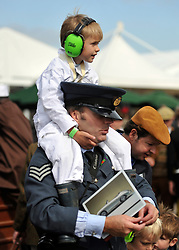 © Licensed to London News Pictures. 17/09/2011. GOODWOOD, UK.  A young boy wears ear defenders to protect from the roar of the engines. The Goodwood Revival at Goodwood in West Sussex today (17 September 2011). The revival is the world's largest historic motor race meeting, which relieves the 'glorious' days of the race circuit. Competitors and enthusiasts all dress in period fashion to enhance the experience. Photo credit : Stephen Simpson/LNP