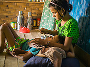 06 NOVEMBER 2014 - SITTWE, RAKHINE, MYANMAR: NOOR AR JUN, 16, feeds her brother, MOHAMMED NOOR, 12, in a private clinic in a Rohingya Muslim IDP camp near Sittwe. The boy has malaria. His parents can't look after him because they are looking for work and food so his oldest sister, Noor, takes care of him. After sectarian violence devastated Rohingya communities and left hundreds of Rohingya dead in 2012, the government of Myanmar forced more than 140,000 Rohingya Muslims who used to live in and around Sittwe, Myanmar, into squalid Internal Displaced Persons camps. The government says the Rohingya are not Burmese citizens, that they are illegal immigrants from Bangladesh. The Bangladesh government says the Rohingya are Burmese and the Rohingya insist that they have lived in Burma for generations. The camps are about 20 minutes from Sittwe but the Rohingya who live in the camps are not allowed to leave without government permission. They are not allowed to work outside the camps, they are not allowed to go to Sittwe to use the hospital, go to school or do business. The camps have no electricity. Water is delivered through community wells. There are small schools funded by NOGs in the camps and a few private clinics but medical care is costly and not reliable.   PHOTO BY JACK KURTZ
