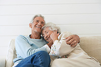 Senior couple cuddling on couch half length