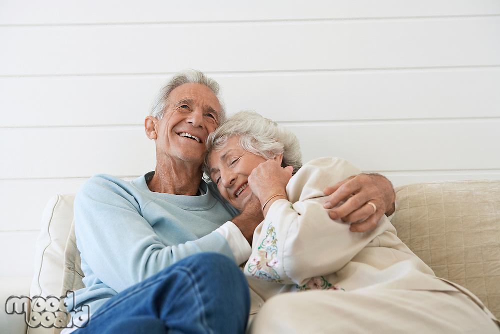 Senior couple cuddling on couch half length