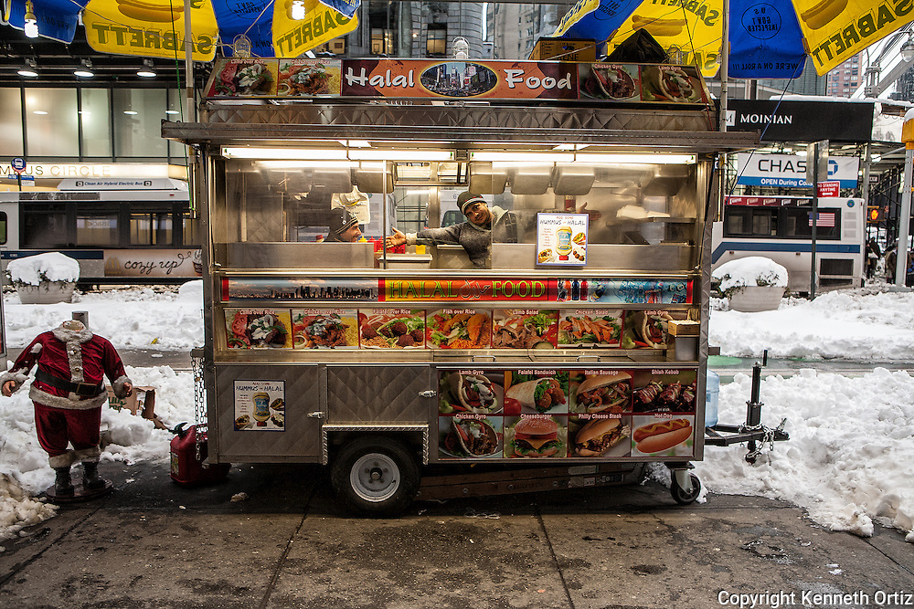 A pair of food vendors wait in their cart early in the morning on Broadway in Midtown Manhattan.