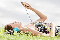 Side view of young woman listening to music through MP3 player while lying on grass against sky
