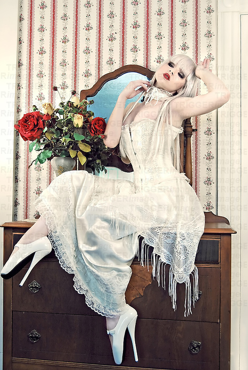 Young woman wearing a white Victorian corset and ballet heels sitting on a Victorian dresser with red lipstick and flowers