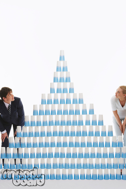 Man and woman admiring pyramid of stacked plastic cups against white background
