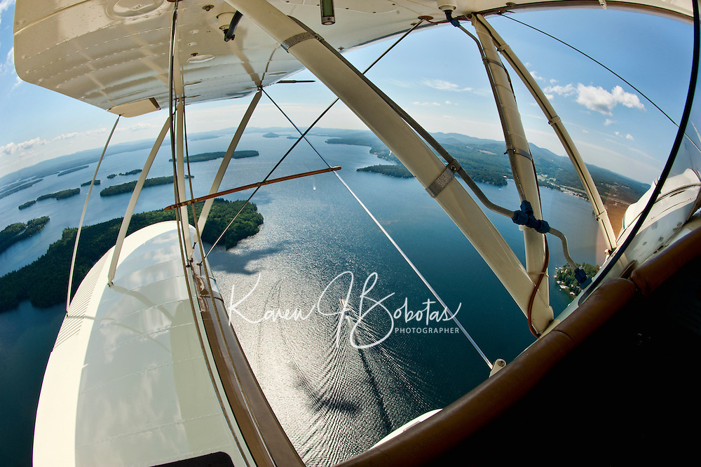 A spectacular birds eye view from the open cockpit of Phil DiVirgilio's Biplane as we take flight over Lake Winnipesaukee Wednesday morning.  (Karen Bobotas/for the Laconia Daily Sun)Taking flight in a WACO biplane with pilot Phil DiVirgilio of Lakes Biplane over Lake Winnipesaukee.