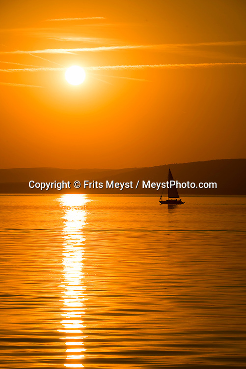 Revfulop, Balaton, Hungary, August 2015.  A sailing yacht during sunrise, sunset. Balatontourist Camping Napfény in Révfülöp is situated directly by lake and at few kilometres from the scenic Kali Basin, considered as the most beautiful landscape of  the Northern shore. Lake Balaton is a freshwater lake in the Transdanubian region of Hungary. It is the largest lake in Central Europe and one of the region's foremost tourist destinations. The mountainous region of the northern shore is known both for its historic character and as a major wine region, while the flat southern shore is known for its resort towns. Photo by Frits Meyst / MeystPhoto.com
