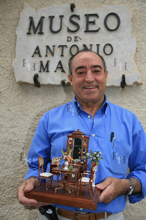 Owner Antonio Marco poses outside Museu do Antonio Marco dollhouse museum with sitting-room diorama; Guadalest, Alicante province, Spain.