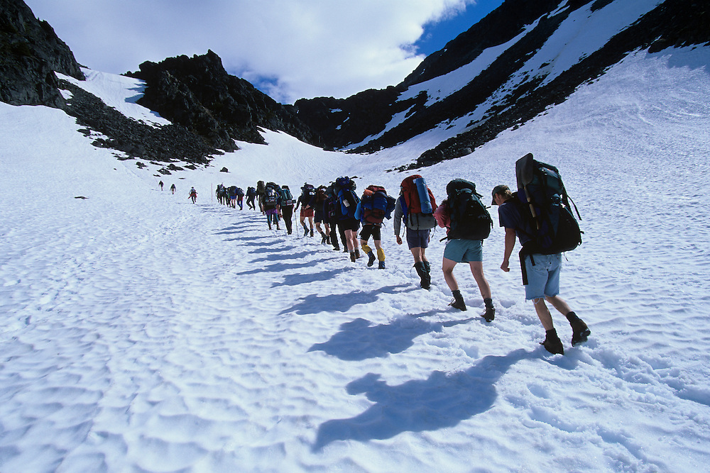 USA, Alaska, Klondike Gold Rush National Historic Park, Line of hikers climb snowy slope to summit of Chilkoot Pass