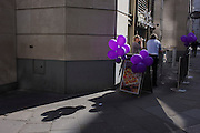 Surrounded by purple balloons, a man and woman drinking outside a City of London wine bar.