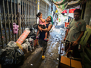 18 SEPTEMBER 2015 - BANGKOK, THAILAND: People walk through the neighborhood near Wat Kalayanamit. They live in the neighborhood and are being evicted from their homes. Fiftyfour homes around Wat Kalayanamit, a historic Buddhist temple on the Chao Phraya River in the Thonburi section of Bangkok are being razed and the residents evicted to make way for new development at the temple. The abbot of the temple said he was evicting the residents, who have lived on the temple grounds for generations, because their homes are unsafe and because he wants to improve the temple grounds. The evictions are a part of a Bangkok trend, especially along the Chao Phraya River and BTS light rail lines. Low income people are being evicted from their long time homes to make way for urban renewal.             PHOTO BY JACK KURTZ