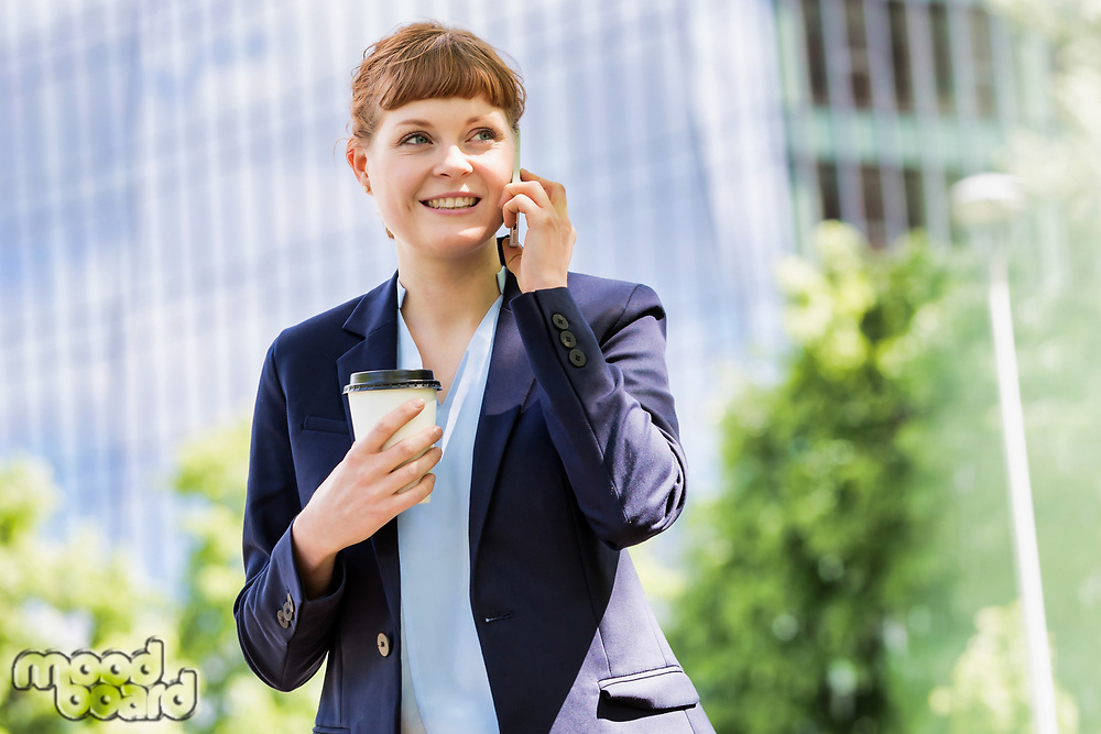 Young attractive businessman holding a cup of coffee while smiling and talking on smartphone