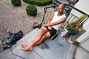 Een wandelaar rust uit nadat hij de 50 km van de Nijmeegse Vierdaagse vor de eerste keer volbracht heeft.