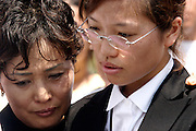 14 SEPTEMBER 2003 - CANCUN, QUINTANA ROO, MEXICO:  The daughters of Lee Kyung-hae comfort each other during a memorial service Sunday for their father, a Korean farm activist who publicly committed suicide Wednesday in Cancun to protest World Trade Organization agricultural policies, has been built where he died in a park in Cancun. Thousands of protestors opposed to the World Trade Organization and globalization have come to Cancun to protest the WTO meetings taking place in the hotel zone. Mexican police restricted most of the anti-globalization protestors to downtown Cancun, about five miles from the convention center.  PHOTO BY JACK KURTZ