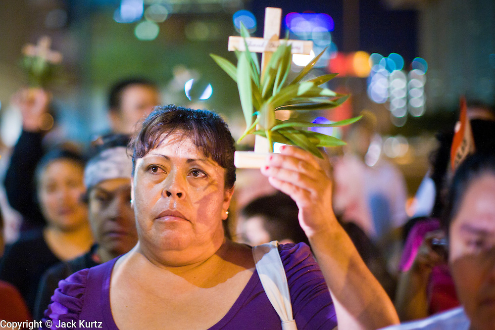 11 OCTOBER 2010 - PHOENIX, AZ:  A woman holds up a cross during a vigil in front of Phoenix police headquarters Monday night. About 300 people gathered at the Phoenix Police Department headquarters building Monday night to protest the shooting of Daniel Rodriguez and his dog. The officers responded to a 911 call made by Rodriguez' mother. A scuffle ensued when they arrived and Phoenix police officer Richard Chrisman shot Rodriguez, who was unarmed, and his dog. Chrisman then allegedly filed a false report about the event. He has been arrested on felony assault charges. The event has angered some in the Latino community and they have held a series of protests at the police headquarters. They want Chrisman charged with murder.    Photo by Jack Kurtz