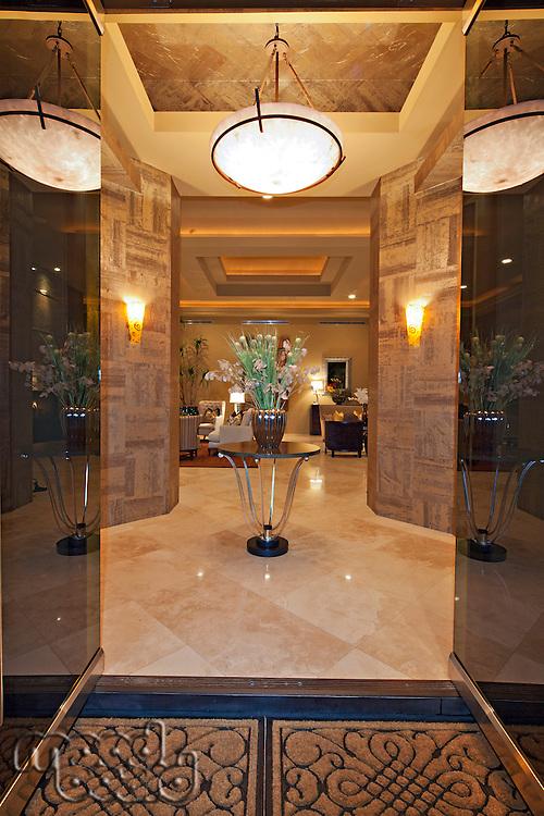 Glass doors open to luxurious foyer