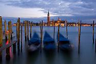 Gondolas at dusk and San Giorgio di Maggiore in the background;  Venice, Italy