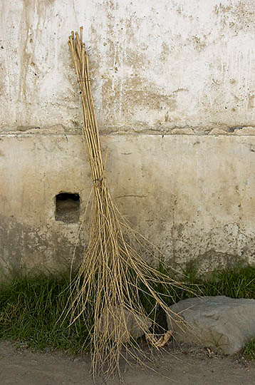 Straw broom against wall. Lhasa, Tibet. Asia.