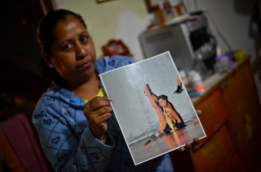 Diana Castro, 50, holds a dance photo of her granddaughter, Yanaifre Acevedo when she was only 12-years old.  Yanaifre, now 15 years old, just gave birth to a baby boy.  Before getting pregnant, Acevedo was a performer, dancing salsa and other sensual dances  to entertain guests at events and parties.