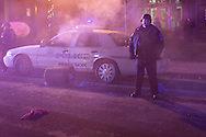 A policeman stands guard as a squad car, set on fire by protestors, burns in front of Ferguson City Hall. Demonstrations turned violent after the grand jury failed to indict Officer Darren Wilson for the shooting death of Michael Brown Jr.