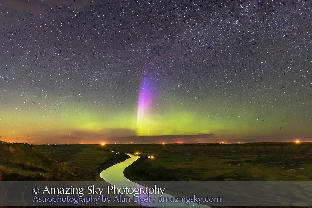 The lone curtain of purple and blue aurora appears briefly amid a broader band of green aurora over the sweeping Red Deer River and Badlands of southern Alberta. From Orkney Viewpoint looking north over the valley. The Bleriot Ferry crossing is in the distance at the lights. Cassiopeia is just above the purple curtain. The river reflects the aurora light. <br /> <br /> This is a stack of 84 x 15-second exposures for the ground to smooth noise, and one 15-second exposure for the sky, all with the 20mm Sigma lens at f/2.8 and Nikon D750 at ISO 3200. They were part of a 250-frame time-lapse.