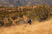 A hiker and their dog passes through dried grassthat lines the Arizona National Scenic Trail in the grasslands in the foothills of the Santa Rita Mountains, Coronado National Forest in the Sonoran Desert, near Sonoita, Arizona, USA. The Arizona National Scenic Trail is a National Scenic Trail from Mexico to Utah that traverses the whole north-south length of Arizona