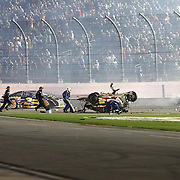 Various crew members run to the car of NASCAR Sprint Cup driver Austin Dillon (3) after he launched into the catch fence on the final lap of the 57th Annual NASCAR Coke Zero 400 stock car race at Daytona International Speedway on Monday, July 6, 2015 in Daytona Beach, Florida.  Dillon walked away from the crash. (AP Photo/Alex Menendez)