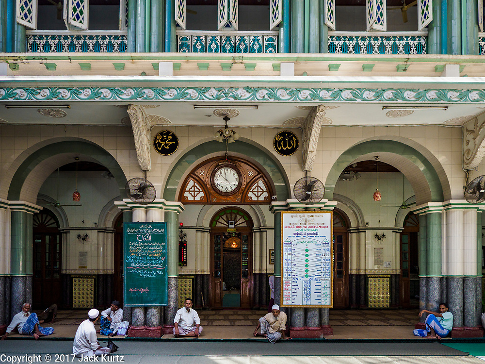 "24 NOVEMBER 2017 - YANGON, MYANMAR: Muslim men wait for Friday midday prayers to start in Surtee Sunni Jumma Mosque in Yangon. Many Muslims in overwhelmingly Buddhist Myanmar feel their religion is threatened by a series of laws that target non-Buddhists. Under the so called ""Race and Religion Protection Laws,"" people aren't allowed to convert from Buddhism to another religion without permission from authorities, Buddhist women aren't allowed to marry non-Buddhist men without permission from the community and polygamy is outlawed. Pope Francis is to arrive in Myanmar next week and is expected to address the persecution of the Rohingya, a Muslim ethnic minority in western Myanmar. Some Muslims and Christians are concerned that if the Pope's comments take too strong of pro-Rohingya stance, he could exacerbate religious tensions in the country.  PHOTO BY JACK KURTZ"