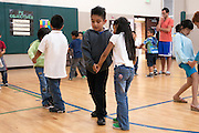 South Park, Washington: July 5, 2011. 1st graders dance in pairs in the gym of Concord International School where they attend a summer program.