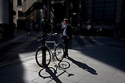 Smoking businessman and locked up bicycle in sunlight corner of a precinct outside a large City of London financial institution in Lime Street.
