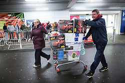 © Licensed to London News Pictures . 27/11/2015 . Salford , UK . Two people with a shopping trolley loaded with coffee machines, remote control cars and stereo equipment from a branch of Tesco in Pendleton , Salford , this morning (Friday 27th November) as people behind queue for Black Friday offers . Last year (2014) scuffles and fights were reported amongst queuing bargain-hunters . Photo credit: Joel Goodman/LNP