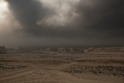 Licensed to London News Pictures. 08/11/2016. Qayyarah, Iraq. A sooty smog fills the air over the town of Qayyarah, Iraq. Oil wells in and around the town of Qayyarah, Iraq, we set alight in July 2016 by Islamic State extremists as the Iraqi military began an offensive to liberated the town.<br /> <br /> For two months the residents of the town have lived under an almost constant smoke cloud, the only respite coming when the wind changes. Those in the town, despite having been freed from ISIS occupation, now live with little power, a water supply tainted with oil that only comes on periodically and an oppressive cloud of smoke that coats everything with thick soot. Many complain of respiratory problems, but the long term health implications for the men, women and children living in the town have yet to be seen. Photo credit: Matt Cetti-Roberts/LNP