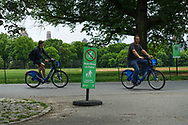 "Bikers speeding past ""Walk Bikes on Paths"" sign at the Great Lawn in Central Park."