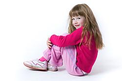 Little girl sitting on the floor smiling,