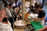 people waiting in line for buying steamed clams at a traditional seafood stall market Kyoto Japan