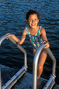 Happy young girl swimming from a lake dock.