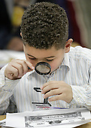 Mechanicstown Elementary School third-grader Nathaniel Garcia uses two magnifying glasses to look at details of an enlarged copy of a dollar bill during a presentation on money and banking by Debra Weaver and Kezia LaBuda of Orange County Trust at the school in Middletown on Jan. 16, 2008.