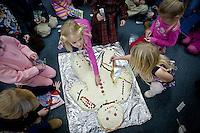 JEROME A. POLLOS/Press..Kate Moorecroft helps decorate an oversized gingerbread man with the rest of her kindergarten class Wednesday at Kinder Magic in Coeur d'Alene. The class carried the decorated treat to share with their pre-school peers after they lit candles and made their Christmas wishes.