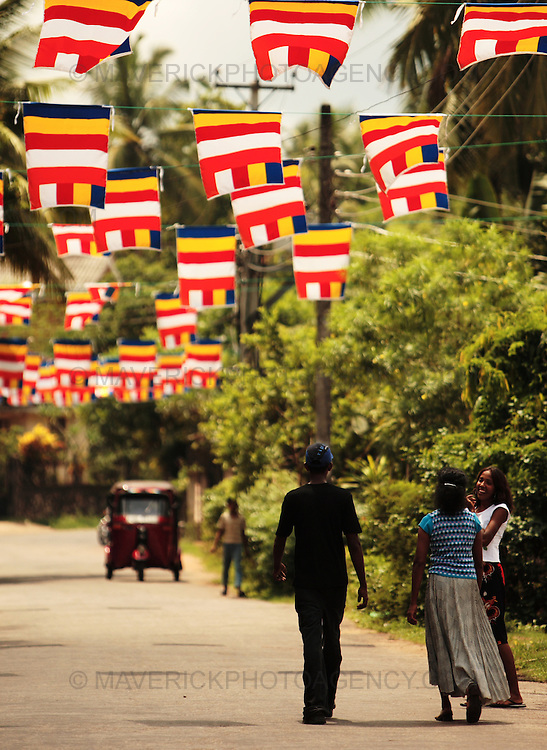 A street is decorated with Buddhist flags for Vesak, Colombo Sri Lanka...Vesak is the most significant period in the Buddhist calendar. It celebrates the birth, enlightenment, and death of the Buddha..email.