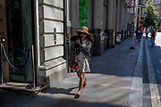 A lady walks along on Threadneedle Street during the 2018 heatwave in the City of London, the capital's historic financial district, on 2nd August 2018, in London, England.