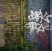 Decaying Victorian brick wall and present-day graffiti in London's east end.