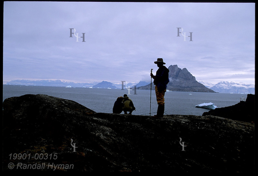 Cruise ship passenger with walking stick stands near couple overlooking distant Uummannaq Island; Qilakitsoq, Greenland