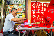"22 JANUARY 2013 - BANGKOK, THAILAND:   A freshly written Chinese New Year greeting flutters in the breeze while a calligrapher works on another at his table on Charoen Krung Road in Bangkok's Chinatown district. Chinese New Year is not an official public holiday in Thailand, but it is one the biggest celebrations in the Bangkok, which has a large Chinese population. Chinese New Year is February 10 this year. It will be the ""Year of the Snake.""    PHOTO BY JACK KURTZ"