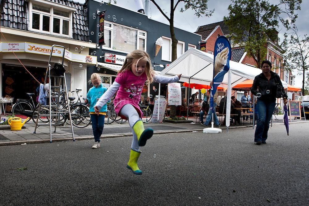 20110618. Braderie in de Oosterpoortwijk. KInderen spelen met de bellen van een bellenblaasapparaat. Op de achtergrond het jubilerende Friet van Piet. foto: Pepijn van den Broeke