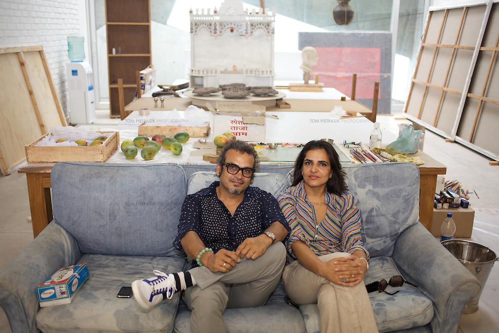 """Contemporary artist husband-and-wife Subodh Gupta and Bharti Kher in Gupta's recently completed studio in the Delhi-satalite town of Gurgaon...Gupta's most celebrated sculptures are constructed from common domestic items including the steel pots and pans that are a feature every Indian home. Of the kitchen-ware that forms the basis of his work, Gupta says,..""""The poor, the middle class and the rich use it at home. In this country, how many people have the utensils but they starve because there is no food?""""..Gupta was brought up, one of six children, to a railway-worker father in a north Indian village. ..Gupta's work fetches such huge sums of money. Two versions of his Mind Shut Down, modeled on the human skull and constructed entirely of steel kitchen utensils recently sold for EUR1 million each...Photo: Tom Pietrasik.Gurgaon, Haryana. India. .July 23rd 2009"""