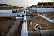 A worker checks valve of pipes connecting panels and factory at Godawari Green Energy Limited Solar-Thermal Power Plant in Nokh, Rajasthan, India on June 9, 2013. 5760 panels of reflective parabolic trough concentrate and reflect the heat on to a receiver tube which contains fluid that is heated to create steam to drive turbines. <br /> (Photo by Kuni Takahashi)